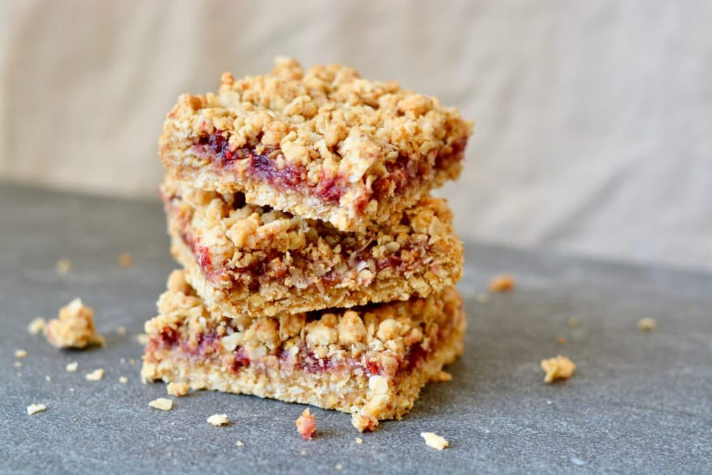 Berry Oat Bars with No Refined Sugar. Simple recipe, ready in less than 30 minutes. Raspberry preserves tucked inside layers of crumbly oat mixture. Perfect for breakfast or dessert!