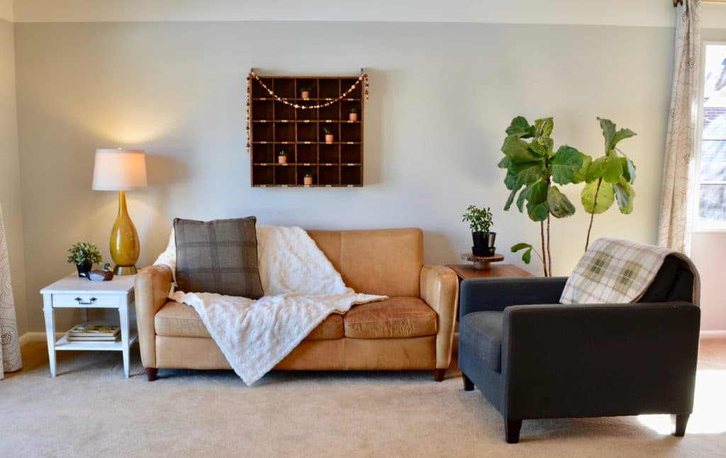Airbnb rental ideas and checklist for renting your primary residence or home. Living space with brown leather couch and fiddle leaf fig.