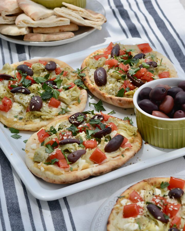 Easy Greek Pizza Recipe - Hummus, Feta, Tomatoes, Kalamata Olives, Artichoke Hearts, Fresh Parsley and Olive Oil.
