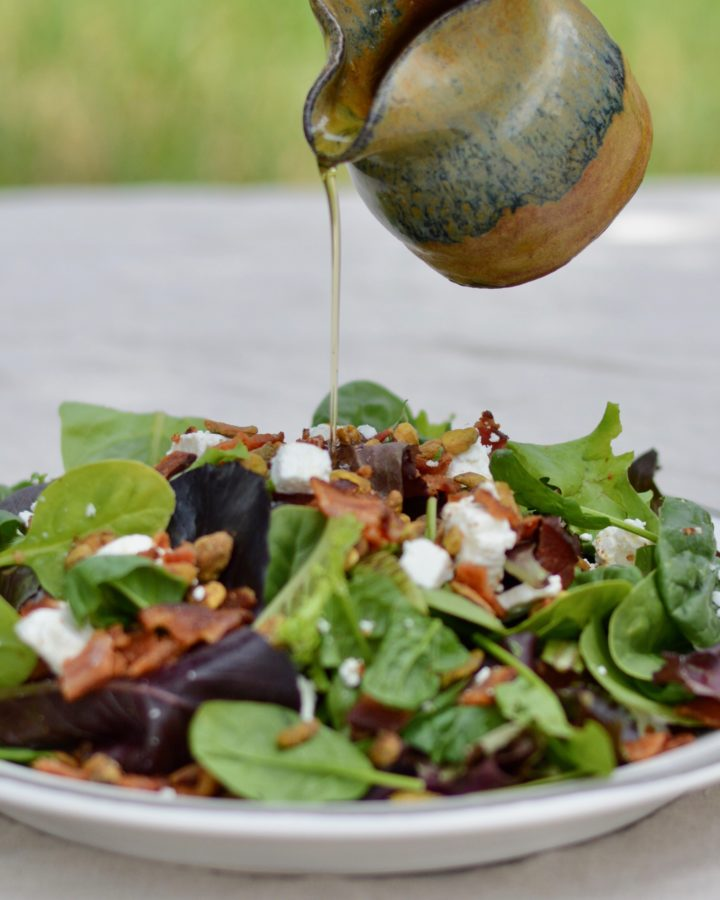 Italian Bacon Salad with warm homemade apricot dressing. Goat cheese, pistachios, bacon and spring mix salad.